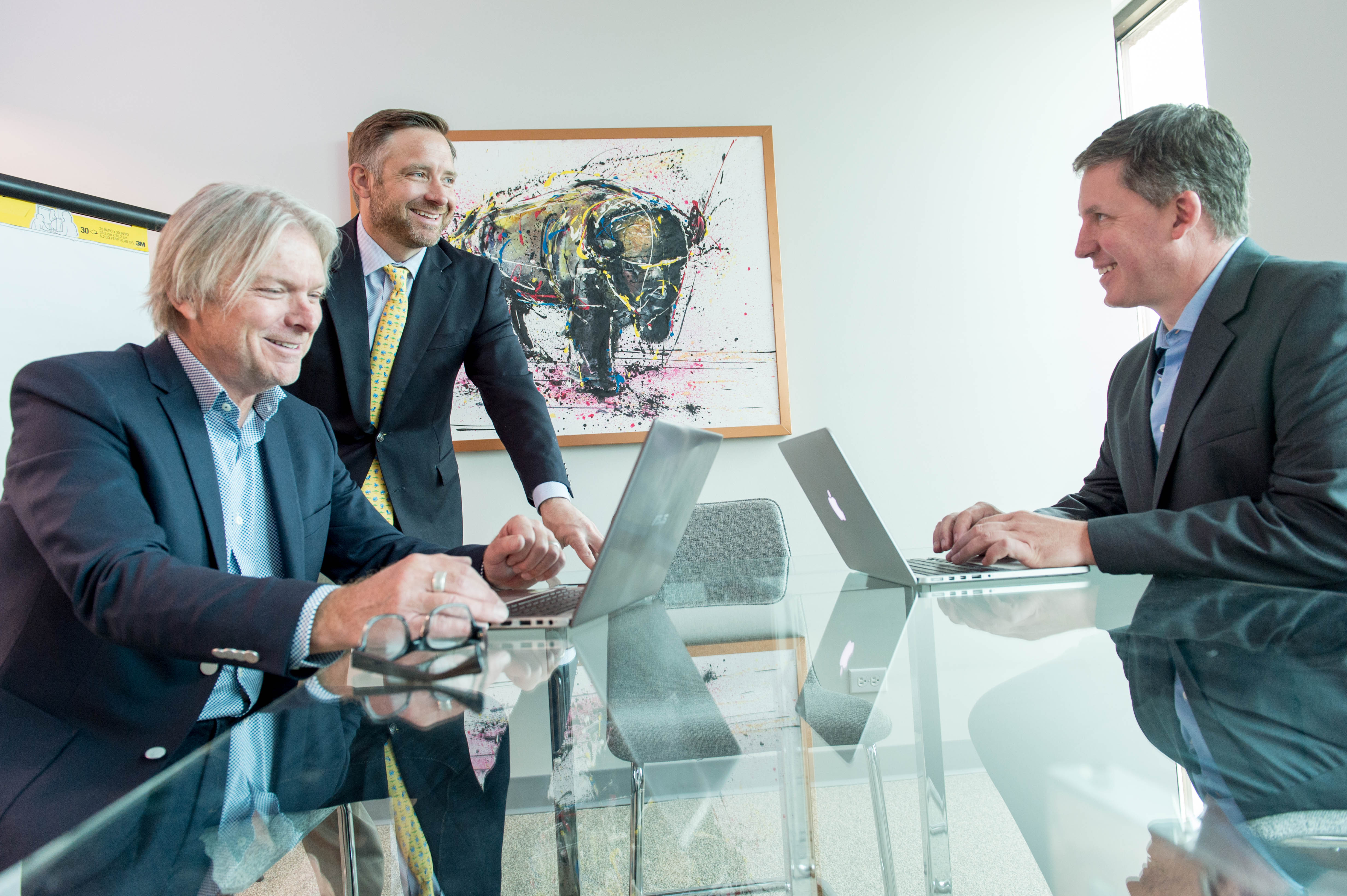 Join Our Team - Commercial Brokerage Team Smiling and Working at a Table