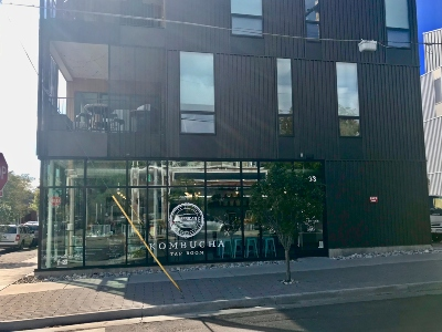 Photo of front of building at 3233 Tejon St in Denver, showing a windowed Kombucha tasting room. This space is available for sublease.