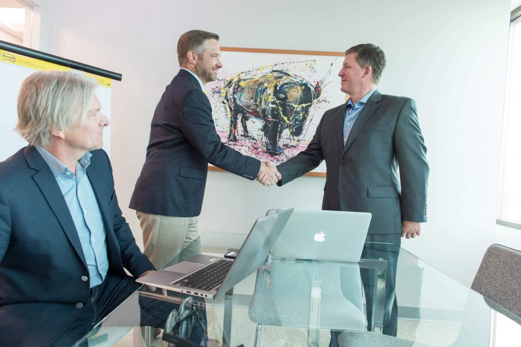 Photo of Transworld Commercial Real Estate Brokers shaking hands. Phil Kubat recently represented a buyer in a commercial property purchase.